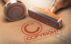 3D illustration of two rubber stamps with copyright word and symbol over kraft paper background, Concept of copyrighted material